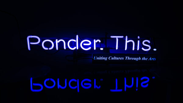 The words Ponder This twice in two shades of purple on a black background