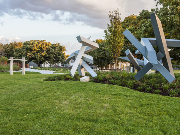 Photo of three sculptures in the Art Garden surrounded by green grass and plantings