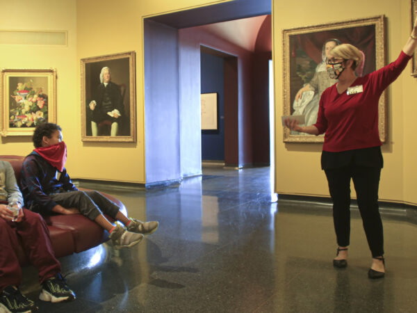 Interior of the galleries with a woman on the right gesturing toward a painting and two young men on the left sitting and watching
