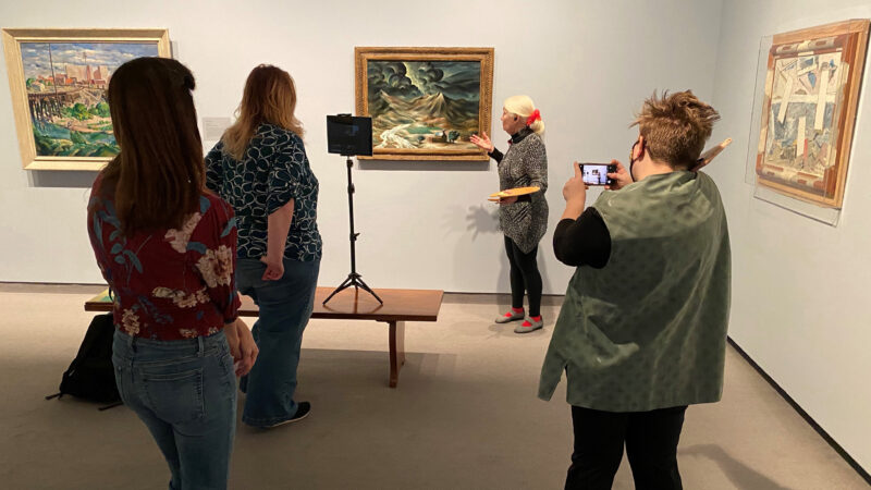 Four women in a gallery looking at art and recording a virtual tour