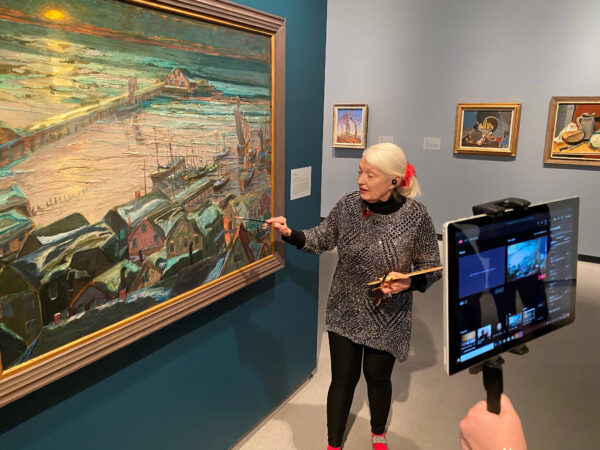Woman in a gallery looking at a landscape painting while talking to the camera and recording a virtual tour