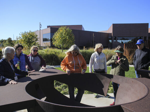 Photograph of a group of people looking at a large-scale circular sculpture of weathered metal in the museum art garden with the museum building in the background