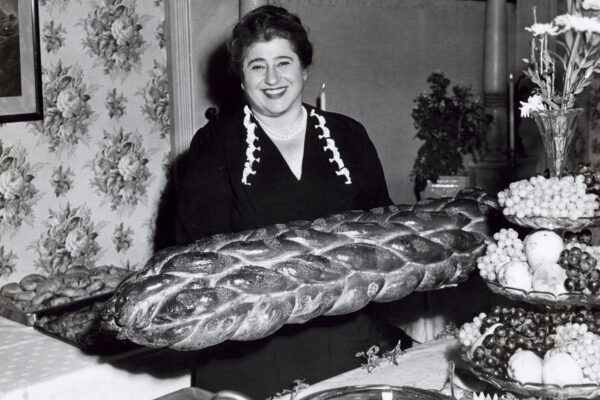 Smiling woman sitting at a table with a large challah bread in front of her and a three-tiered serving bowl with grapes and other fruit and topped with cut flowers