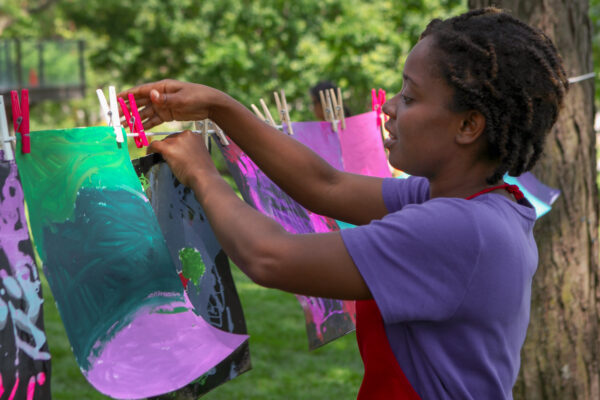Girl in purple shirt and red apron hanging an anstract artwork on a string tied to a tree in the Art Garden