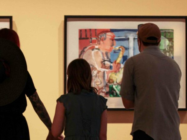 Three people, adult woman holding the hand of a young girl and adult man, in silhouette in front of colorful painting of a saxophone player in a gallery