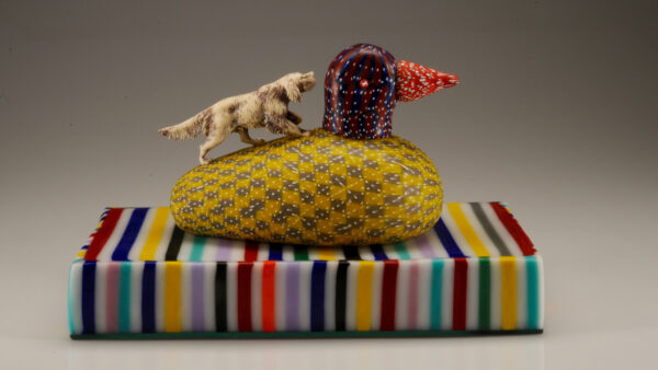 Colorful glass base with duck on top of it and a dog on the left climbing up the back of the duck