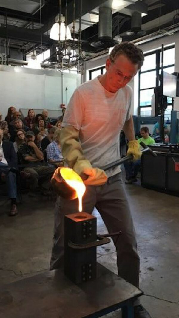 Photograph of a man pouring molten glass into a mold in front of an audience.