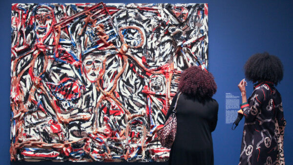 Two women with their backs towards the camera look at an abstract painting against a blue gallery wall