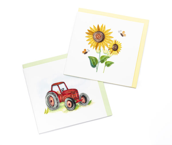 White notecard with a tractor on the left and two sunflowers on the right
