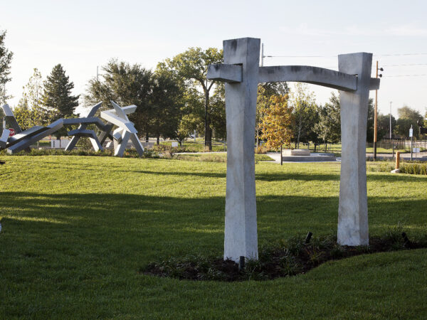 Exterior Art Garden with green grass, a walking path and a large marble sculpture in the foreground with steel sculptures in the background