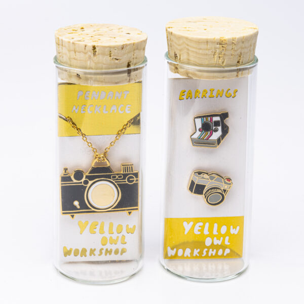 Two glass vials with cork tops and camera necklaces in black and gold inside each vial with the words pendant necklace and earrings on tags inside along with the company name Yellow Owl Workshop
