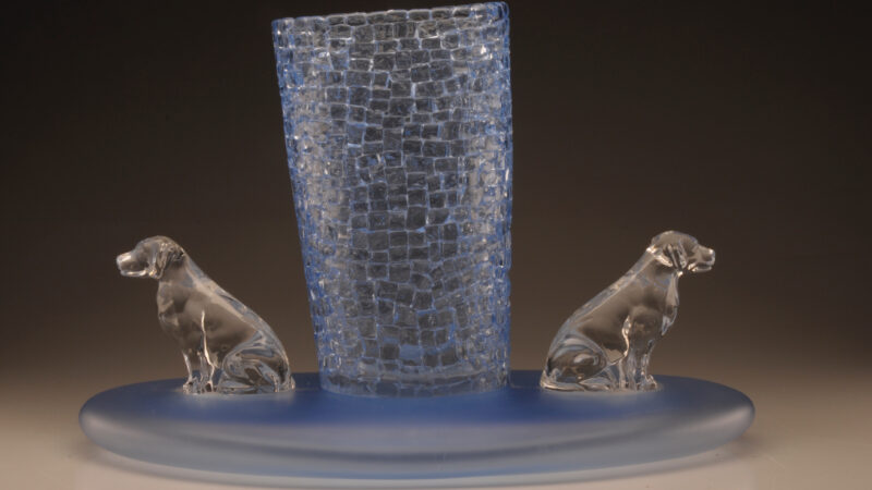 Light blue vase in the center with two clear, glass dogs on either side, sitting atop a light blue round glass base