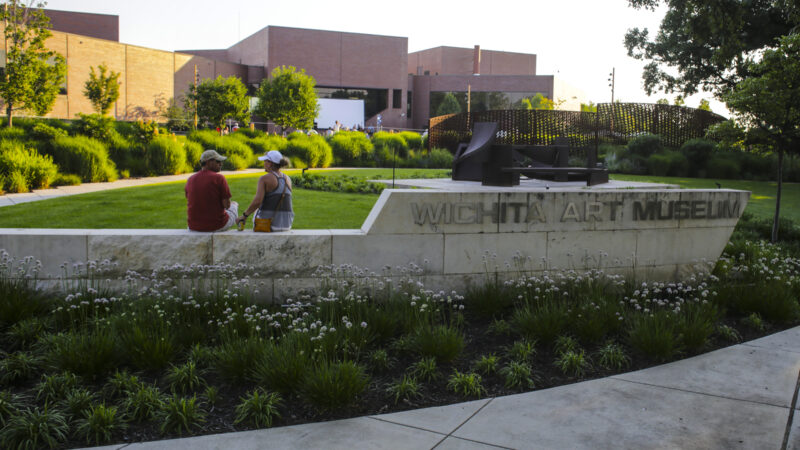 Photo of two people with their backs to the camera sitting on the limestone sign for the Wichita Art Museum with the Art Garden in the background