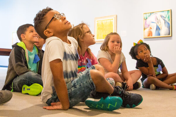 Group of children sitting on the floor. Boy in the foreground has dark, curly hair and is wearing glasses, sitting cross-legged and looking up.