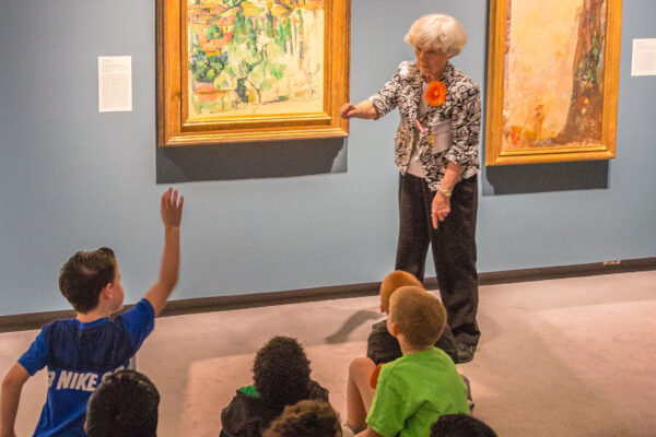 Group of seven younger students sitting on the floor in a gallery, in front of two paintings. An older, white-haired woman stands in front of them, one hand outstretched toward the group and the other pointing toward the artwork on the wall beside her.