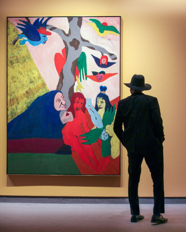 Man standing in front of a large painting in the African American Art in the 20th Century exhibition with his back to the camera
