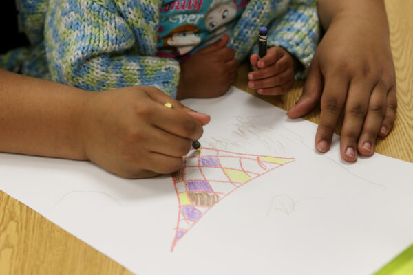 Photo of a mother's hands helping her child's hands draw with colored pencil on a white piece of paper