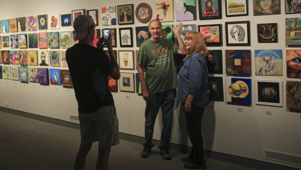 Two people standing in front of a wall of 12x12-inch paintings from the Foot in the Door exhibition while another visitor takes their photo
