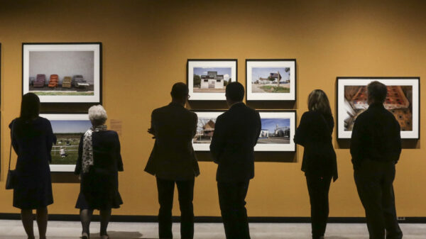 Photo of six museum vistors standing in front of a dark yellow wall looking at seven photos from the Kansas Land exhibition