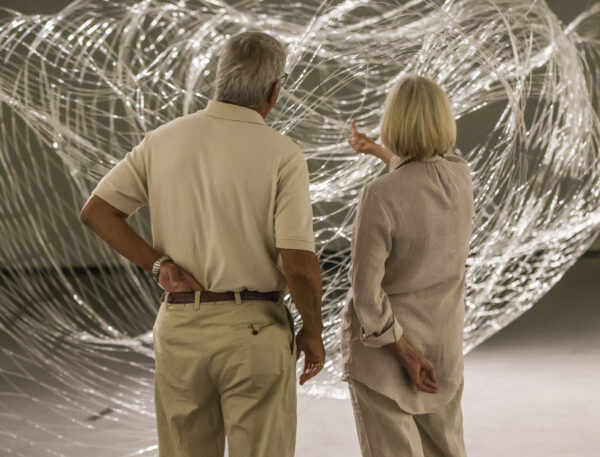 Man and woman standing in front of a large-scale glass sculpture