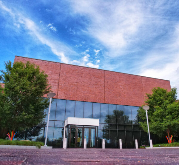 Photo of the museum's glass and brick entrance with trees on either side of the front doors