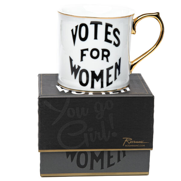 White coffee cup with the words Votes for Women on the front in a black font and sitting atop a black box