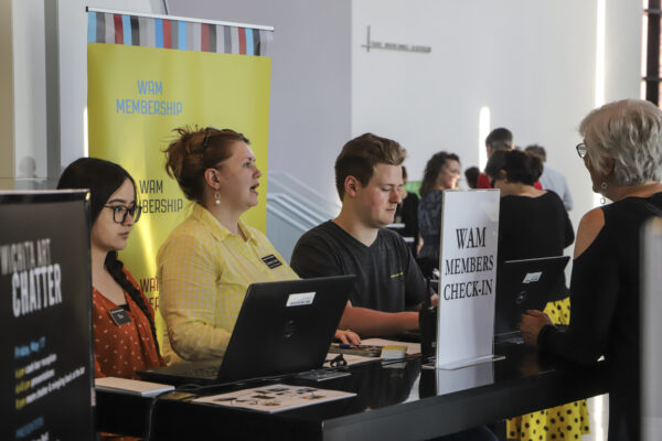 Three museum staffers standing behind a table and checking in event attendees using laptops
