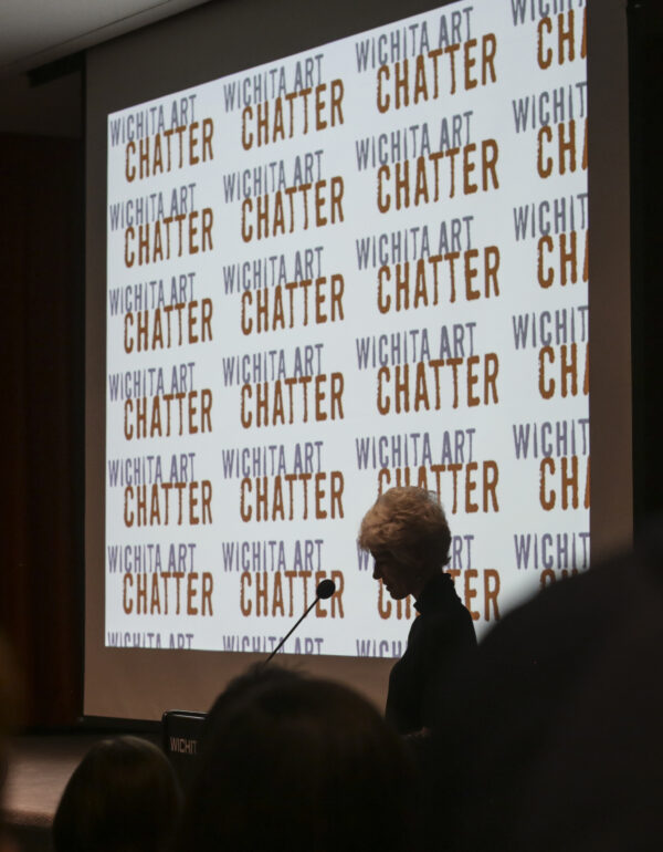 Photo of a woman in shadow standing in front of a projection screen in the darkened Howard E. Wooden Lecture Hall with the words Art Chatter projected onto the screen