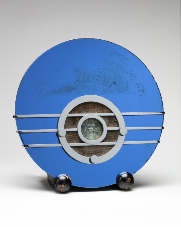 Round blue radio with silver speaker and control knobs on two shiny round black feet