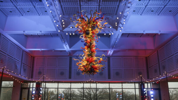 Photo of the colorful, large-scale Chihuly Chandelier in the S. Jim and Darla Farha Great Hall with small, white lights hanging from the ceiling around it and large windows in the background