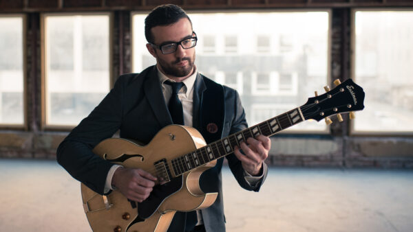 Photograph of a man dressed in a dark suit, white shirt and dark tie playing a guitar. He is standing in front of a bank of windows with a hazy urban landscape.