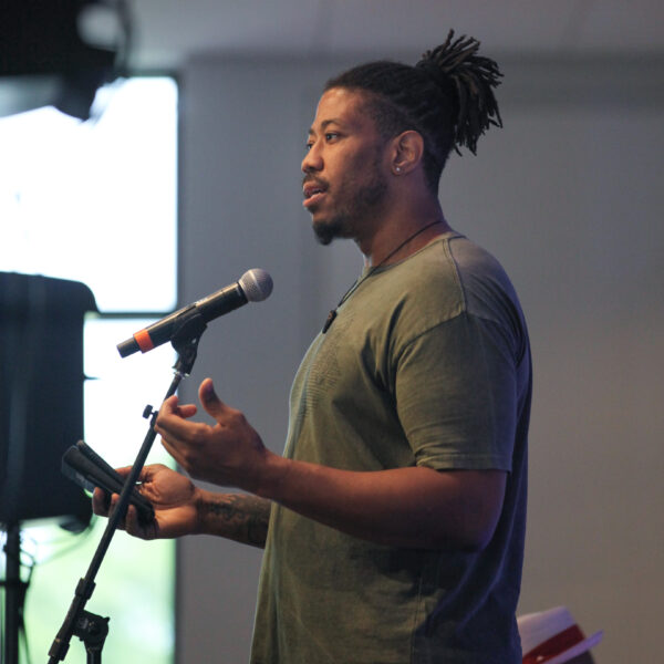 Photograph of African American man standing in front of a microphone, arms held in front of his torso with palms up. His dark hair is tied in a bun at the top of his head and he wears an olive green t-shirt