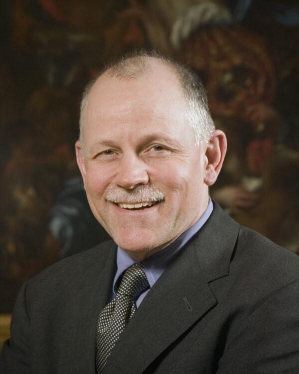 Portrait of a man wearing a dark suit and dark gray tie.