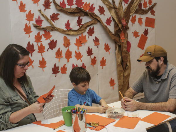 Photograph of two adults and a child sitting at a table with shades of light brown paper, markers, and scissors in front of them. An image of a tree with various leaves of browns and reds is on the wall behind them.