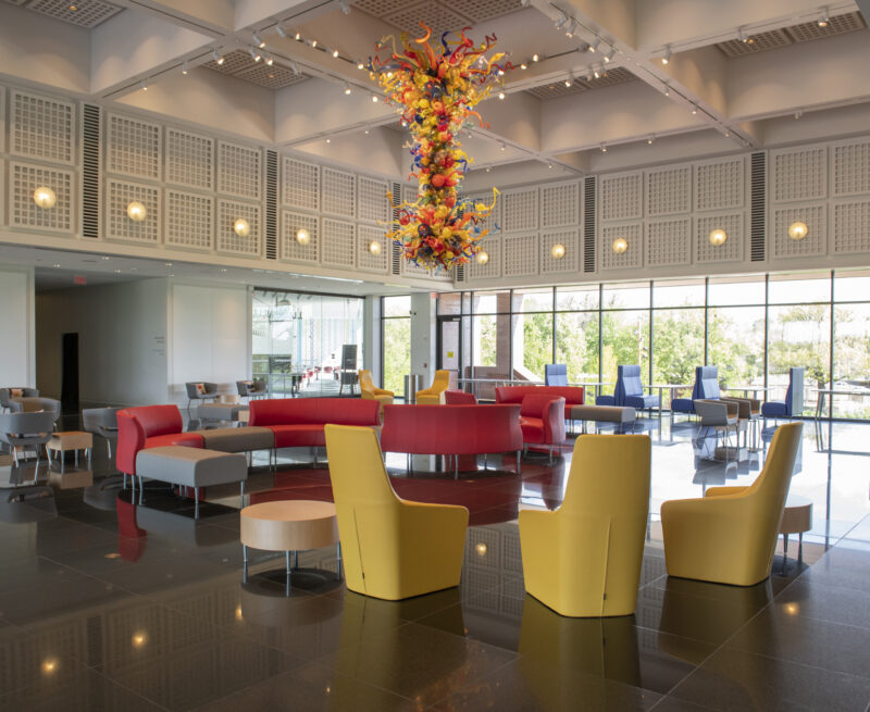 Photo of the S. Jim and Darla Farha with a dark granite floor, yellow chairs in the foreground, red couches in the middle and blue booths against the windows at the back of the hall with colorful glass Chihuly chandelier hanging from the ceiling