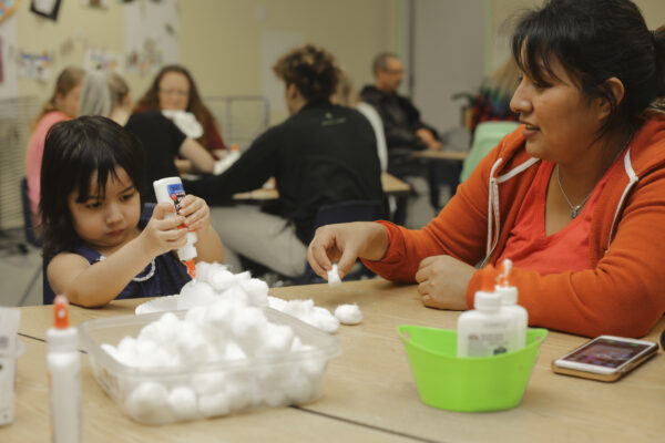 A child with dark hair, seated at a table with a pile of white cotton balls in front of her. She holds a bottle of glue upside down. Seated to her left is a dark-haired woman, dressed in an orange top, one hand reaching out toward to girl with a cotton ball.