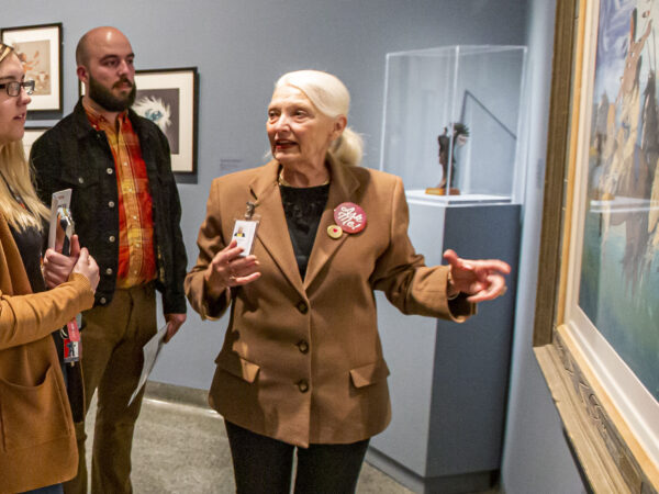 Photograph of people int the gallery. Woman at right has long blonde hair, dark-rimmed glasses and is wearing a tan coat. Man int he middle is bald with a dark beard, wearing an orange and yellow shirt under a dark jacket. Woman at right, standing in front of a painting, has white hair pulled back into a ponytail and is wearing a tan jacket over a black shirt. Her arm is outstretched with palm up toward the painting