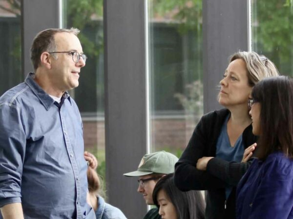 Photograph of a man and two women standing in front of floor-to-ceiling windows. The man has light brown hair and is wearing glasses, dressed in a blue, long-sleeved shirt with the cuffs rolled to his elbows. The woman in the center has light brown hair andis dessed in a dark sweater. The woman on the far right has shoulder length dark hair and is wearing a dark purple top.