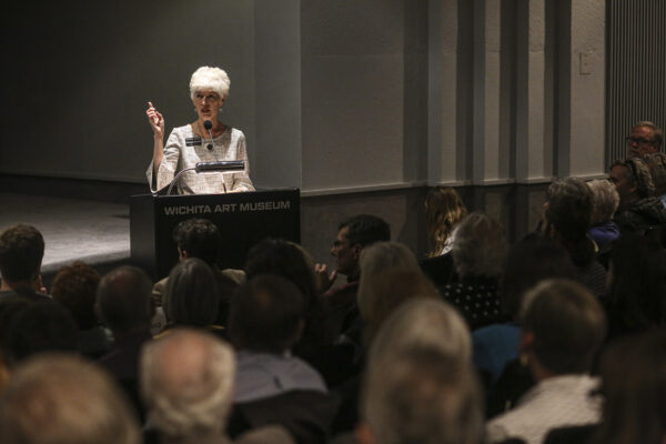 Photo of a woman standing at a podium gesturing with her right hand in front of a crowded lecture hall with several dozen people