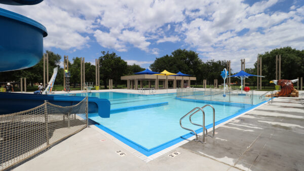 Photo of a pool with blue and yellow sunshades