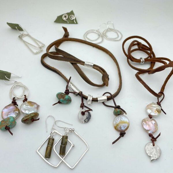 Assortment of jewelry featuring silver, stones and leather cord