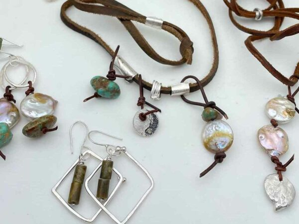 ssortment of jewelry featuring silver, stones and leather cords