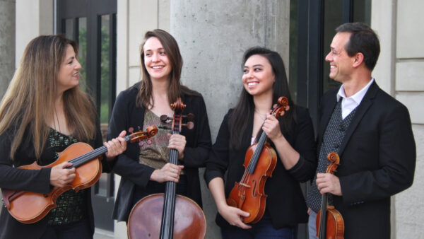 photograph of four people in an outdoor setting in front of a granite column. From left, woman with long dark hair, dressed in black and holding a viola, next is another woman with shoulder length dark hair, dressed in a black jacket over a lighter print and the fret and top of a cello in front of her. the third person is a woman with long, dark hair, dressed in black and holding a violin. The fourth person is a dark-haired man dressed ina black jacket and white shirt and holding a violin.